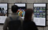 서울 중구 서울도서관 외벽에 서울시와 함께하는 2020 서울글로벌포토저널리즘 사진전이 설치되어 출근하는 시민들이 지나가며 보고 있다.