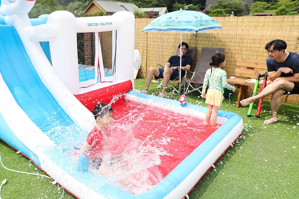 <p>전국적으로 폭염이 이어진 29일 오후 경기 용인 원삼면 한 주택에서 어린이들이 물놀이를 하고 있다. 코로나19 재확산과 기록적인 폭염이 이어지면서 집에서 머물며 시원하게 여름을 보내는 홈캉스(홈+바캉스)가 각광받고 있다. <br></p>