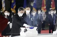 방미 일정을 마치고 귀국한 문재인 대통령이 23일 밤 경기 성남시 서울공항에서 열린 국군 전사자 유해 봉환식에서 유해 위에 참전기장을 올리고 있다.