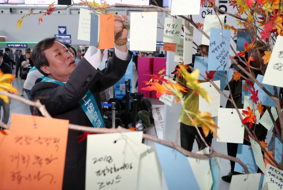 도종환 문화체육관광부장관이 추석 연휴를 하루 앞둔 9월 29일 서울역에서 열린 2018평창동계올림픽대회 홍보행사에 참석해 올림픽 성공기원 메시지를 행운의 나무에 걸고 있다.