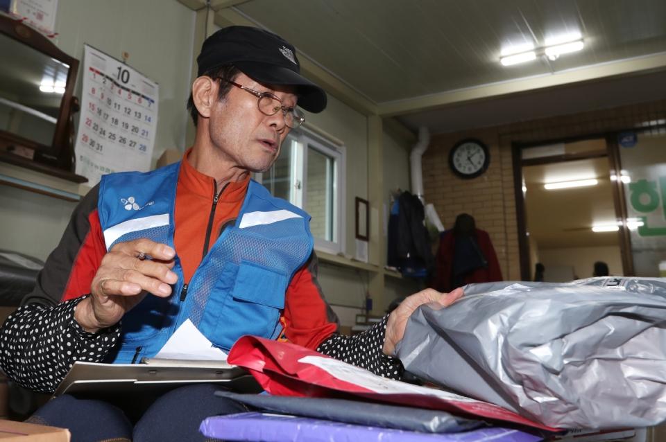 10월 17일 서울시 상계주공14단지 경로당에서 CJ 대한통운 실버택배 사업에 참여하는 어르신들이 택배물건이 도착하자 물건을 정리하고 있다. 이날 어르신(이은호, 만77세)이 맡은 물건을 배달 전에 꼼꼼히 파악하고 있다.