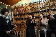 문재인 대통령 부인 김정숙 여사가 12월 13일 오후 중국 베이징 신제커우 악기거리의 세기아운금행에서 중국 전통악기 '얼후'를 체험하고 있다.