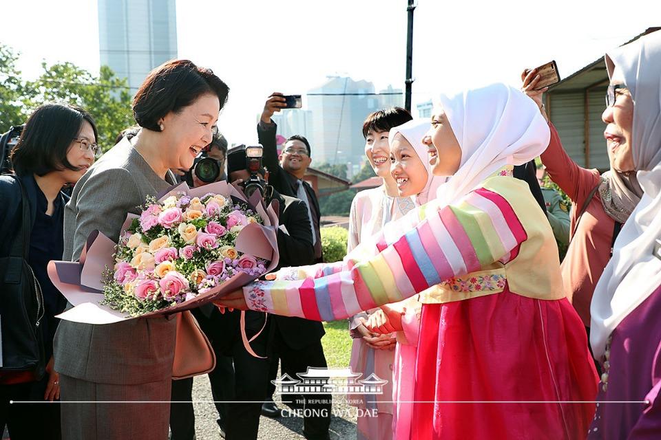 말레이시아를 국빈방문 중인 문재인 대통령의 부인 김정숙 여사가 14일 오전(현지시간) 말레이시아 쿠알라룸푸르 스리푸트리 여자 과학 중등학교를 방문, 한복을 입은 현지 학생에게 꽃다발을 건네받고 있다.