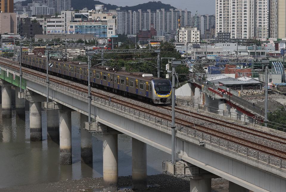 지난 9월 10일 25년 만에 수원~인천 복선전철인 수인선 개통식이 열렸다. 15일 인천시 남동구 소래포구 인근 고가를 수인선 전동차가 지나고 고가 옆에 옛 소래철교로 시민들도 지나가고 있다.