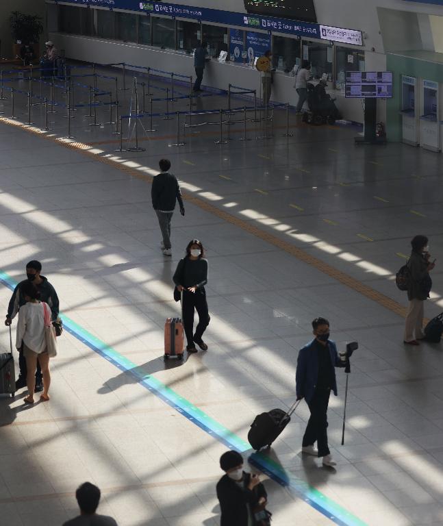 추석 연휴를 하루 앞둔 29일 오전 서울역이 비교적 한산한 가운데 시민들이 고향을 가기 위해 탑승 열차로 걸어가고 있다. 이날 KTX 열차 내 좌석 간 띄어앉기로 탑승 승객들이 창가 좌석에 앉아 출발을 기다리고 있다