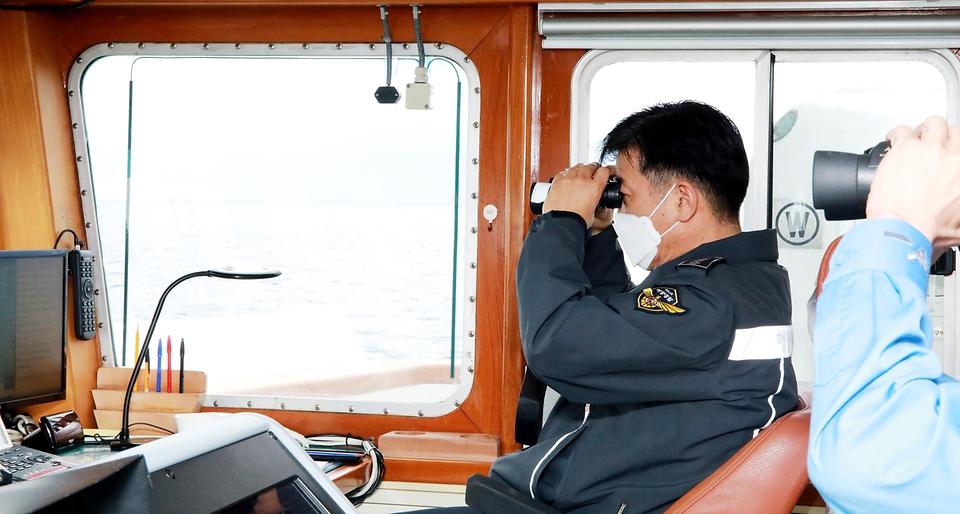 김홍희 해양경찰청장이 불법 외국어선의 진입을 차단하며 강력 대응하는 3008함에서 중국어선을 확인하고 있다.