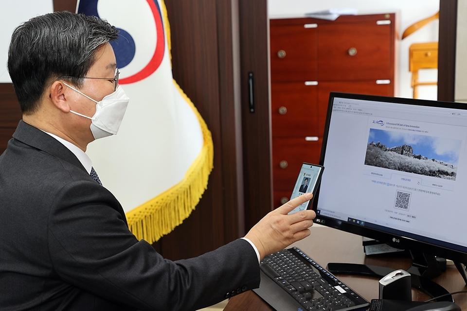 전해철 행정안전부 장관이 13일 오전 정부세종2청사 집무실에서 모바일 공무원증으로 행정안전부 업무시스템에 로그인을 시연해 보고 있다.