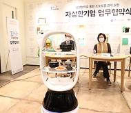 박영선 중소벤처기업부 장관(가운데)이 18일 서울시 송파구 배민아카데미에서 열린 '상생협력을 통한 프로토콜 경제 실현'을 위한 자상한 기업 업무협약식에서 협약서에 배달로봇이 배달한 서명펜을 받고 있다.
