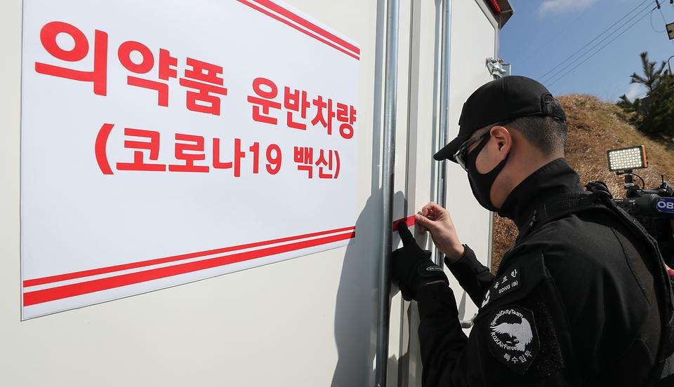 28일 울릉도 해군부대 헬기장에 도착해 울릉도 보건소로 옮겨지는 차량을 백신수송지원본부 장병이 봉인하고 있다.