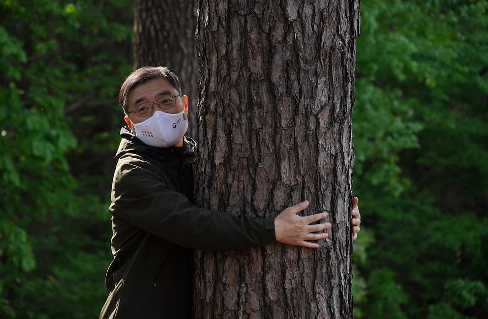 최병암 산림청장이 13일 오후 경북 울진군 금강소나무 숲을 찾아 산림의 생태적 관리와 국가 보호지역 관리 강화 방안에 대해 관계자들과 논의한 후 아름드리 소나무를 안아보고 있다.