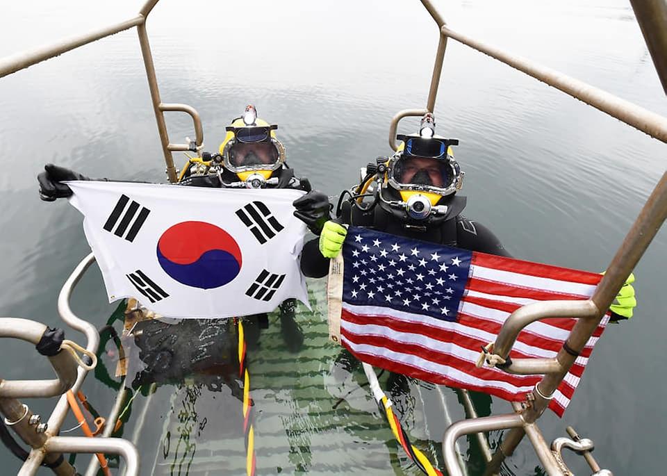 15일 경남 창원 진해만 일대에서 열린 한미 연합 구조전 훈련에서 양국 구조대원들이 손상 함정 긴급 복구 훈련 종료 후 자국 국기를 들어보이고 있다. (출처=대한민국 해군 페이스북)