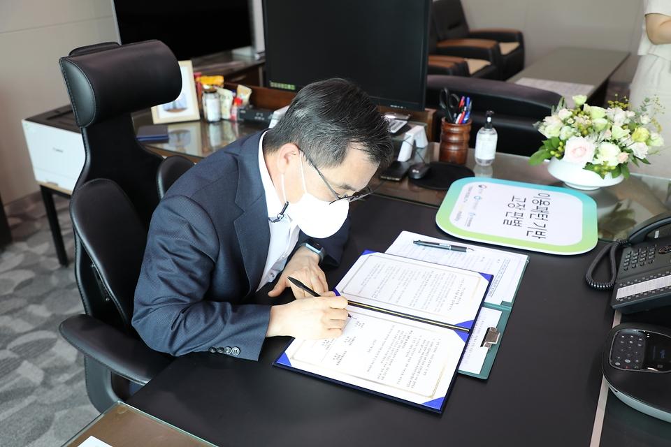 홍정기 환경부차관이 29일 오후 비대면(untact) 영상으로 진행된 '전기자동차 충전시설 스마트 서비스 제공을 위한 업무협약식'에 참석하여, 협약서에 서명하고 있다.