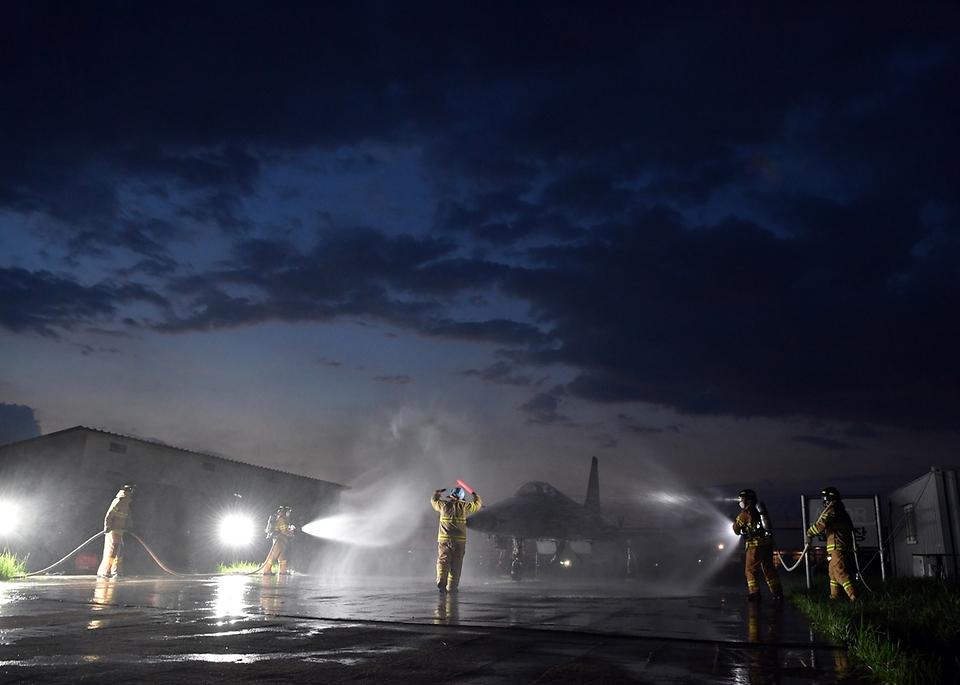 공군 38전투비행전대 소방구조반 요원들이 27일 야간 항공기 화재 상황을 가정한 훈련에서 F-5 전투기에 물을 뿌리고 있다.