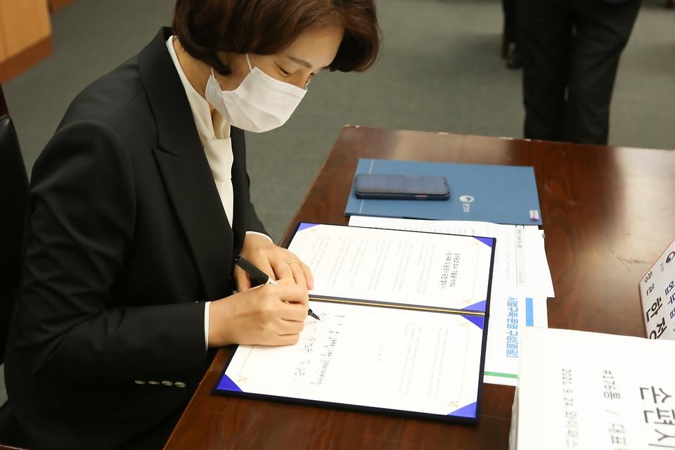 한정애 환경부장관이 24일 오전 서울 강북구청에서 개최된 '담배꽁초 회수·재활용 시범사업 업무협약식'에 참석하여 협약서에 서명하고 있다.