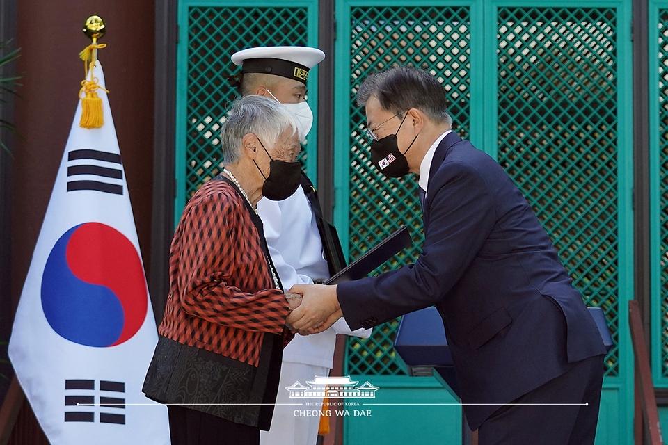 문재인 대통령이 22일(현지시각) 미국 하와이대 한국학 연구소에서 열린 독립유공자 훈장 추서식에서 독립유공자 김노디 지사 후손에게 애국장을 수여하고 있다.