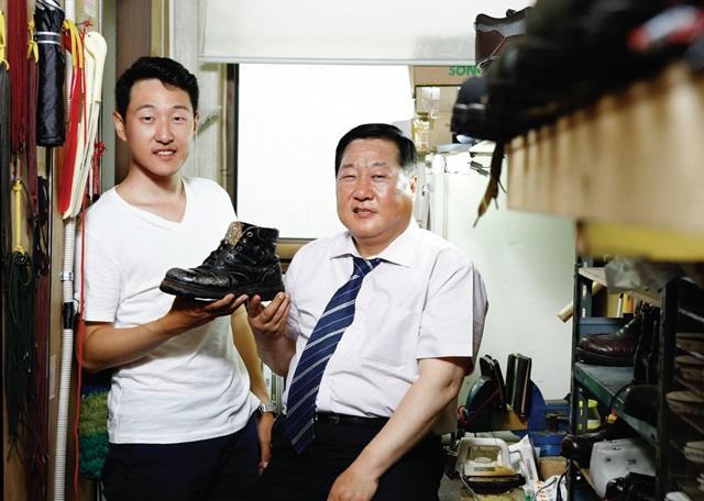 송림수제화 3대 장인인 임명형(53) 사장과 그의 아들 임승용(25) 씨가 1950년대 제작된 것으로 추정되는 등산화를 들고 있다