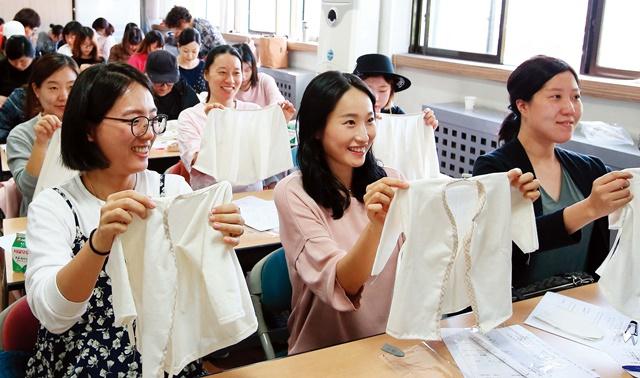 '임산부의 날' 행사에 참석한 임산부들이 아기를 위해 만든 배냇저고리를 들어 보이고 있다.