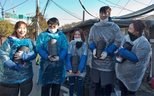 반복되는 작업에도 연신 미소를 띠며 연탄을 운반하고 있는 자원봉사자들