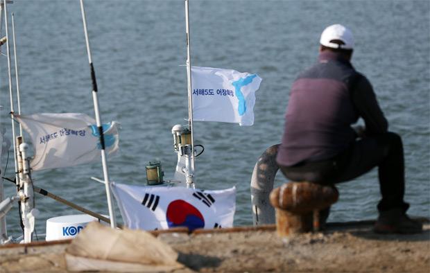 한 연평도민이 어선에 매달린 서해 5도 한반도기를 보고 있다.