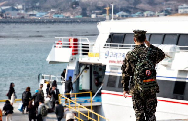 한 군인이 인천행 배에 오르는 주민들을 향해 거수경례를 하고 있다.