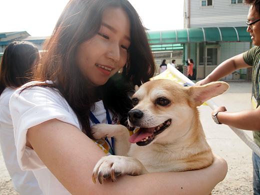입양의 날 행사에서 강아지를 입양한 한 여성이 행복한 표정으로 입양견을 안고 있다.