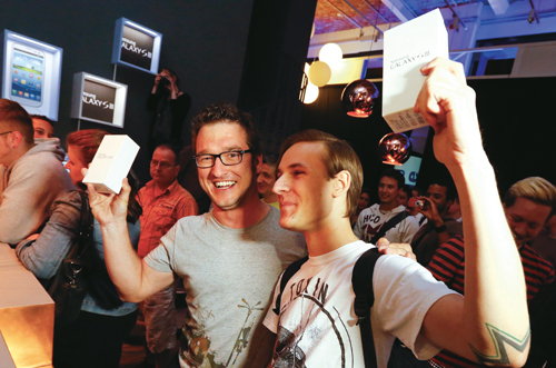 지난 5월 29일 독일 베를린에서 삼성전자 갤럭시S Ⅲ를 구입한 소비자들이 제품을 들어보이며 기뻐하고 있다.