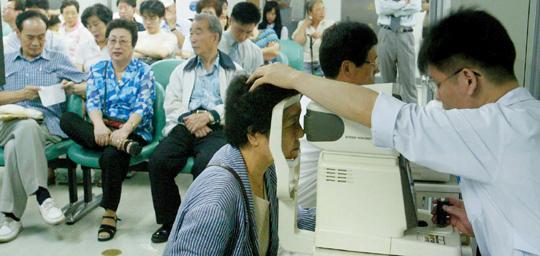 여름철의 대표적인 불청객인 결막염이 의심되는 한 환자가 병원을 찾아 전문의에게 치료받고 있다.
