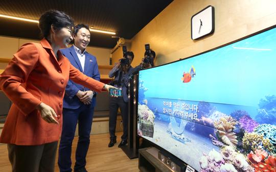 박근혜 대통령이 15일 오전 대구 무역회관에서 열린 창조경제혁신센터 확대 출범식에 참석, 혁신센터를 둘러보던 중 스마트폰의 '3D 오션 앱'을 이용해 TV 속 가상 물고기에게 먹이를 주고 있다. (사진=저작권자 (c) 연합뉴스. 무단전재-재배포금지)