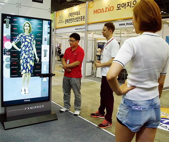 6월 22일 경기 고양시 킨텍스에서 열린 증강현실 및 가상현실 분야 국제 콘퍼런스인 '증강현실 서밋'에서 관람객들이 증강현실을 이용한 3D 가상피팅을 체험하고 있다.(사진=동아DB)