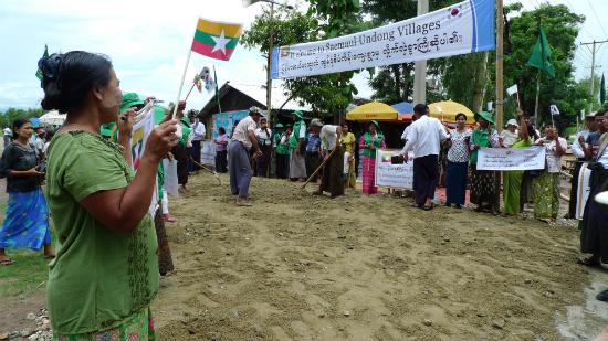 미얀마 네피도 근교의 새마을운동 시범마을인 칸 따르 마을에 7일 한국국제협력단 등 한국 방문객을 환영하는 플래카드가 내걸린 가운데 주민들이 도로포장 작업을 벌이고 있다. <저작권자(c) 연합뉴스, 무단 전재-재배포 금지>