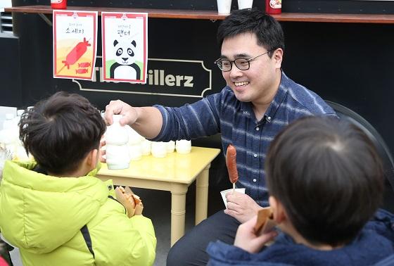 함현근 칠링키친 대표가 어린이들에게 '꾸야 꾸야 소세지와 하얀마음 팬더 우유'를 나눠주고 있다.