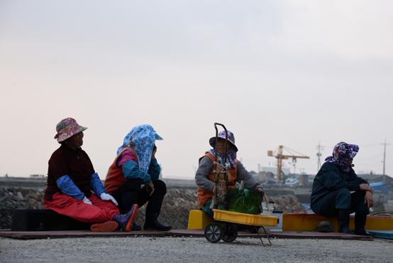 어촌계장의 방송소리를 듣고 조개를 파기 위해 나온 어머니들이 물이 빠지기를 기다리고 있다.