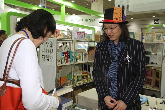 서울국제도서전에 참여한 서울 '이상한 나라의 헌책방' 서점의 윤성근 대표가 서점 부스를 찾은 사람들에게 책을 소개하고 있다.
