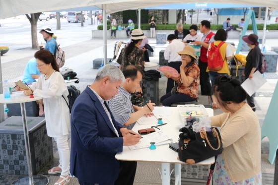 서울 세종로 한글공원에 마련된 광화문 1번가 열린광장에서 국민들이 정책제안서를 쓰고 있다.