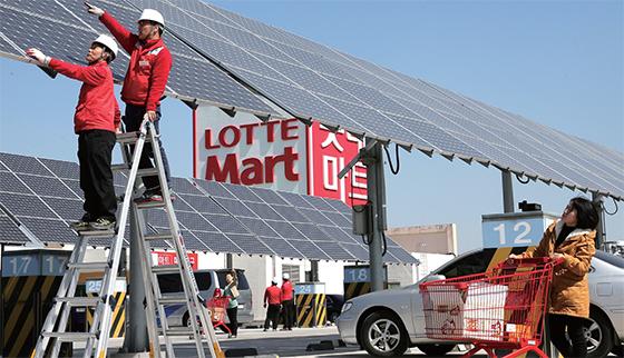 2015년 3월 23일 서울 롯데마트 구로점 옥상에 설치된 태양광 발전장치를 직원들이 점검하고 있다. 롯데마트는 전국 39개 점포 옥상에 태양광 발전장치를 운영해 작년 전력량 451만kwh를 생산했다.(사진=조선DB)