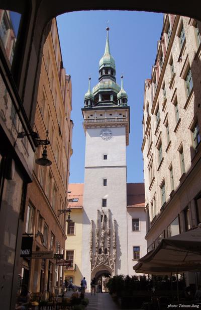 골목에서 본 브르노 구시청사의 탑. 입구문 장식의 끝 부분이 구부러져 있다.