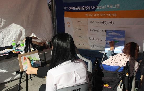 지체장애 3급 김세라 화가와 지체장애인의 어려움을 체험하고 있는 한지호 학생