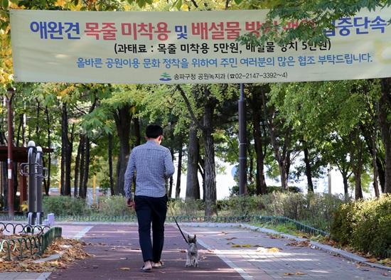22일 오후 서울 송파구의 한 공원에 반려견의 목줄 미착용 및 배설물 방치 행위를 단속하는 내용의 현수막이 걸려 있다.(출처=뉴스1)