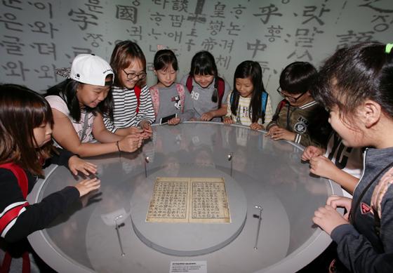학생들이 서울 용산구 국립한글박물관을 방문해 '한글이 걸어온 길'상설전시관에 전시되어 있는 복제된 '훈민정음(해례본)'을 보고 있다.