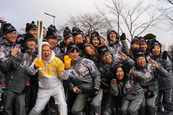청년들과 함께 기념사진을 찍는 94번 주자 데니스 홍 교수