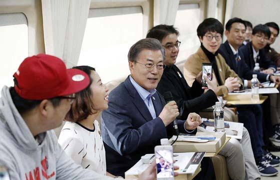 문재인 대통령이 19일 서울~강릉행 KTX 열차에서 '헬로우 평창' 이벤트 당첨자들과 이야기하고 있다. (사진 = 청와대)