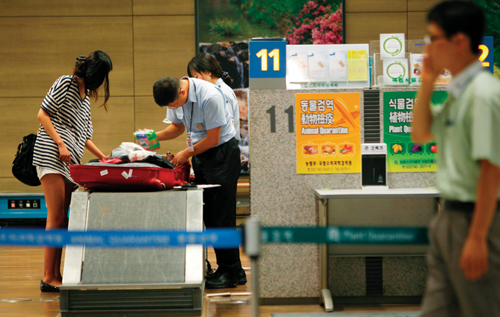 인천공항 검색대에서 관세청 직원이 승객들의 수하물과 휴대용 가방을 살펴보고 있다.