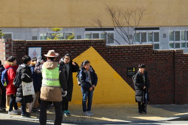 학생들의 하교 모습. 옐로우 카펫 안에 서있다.