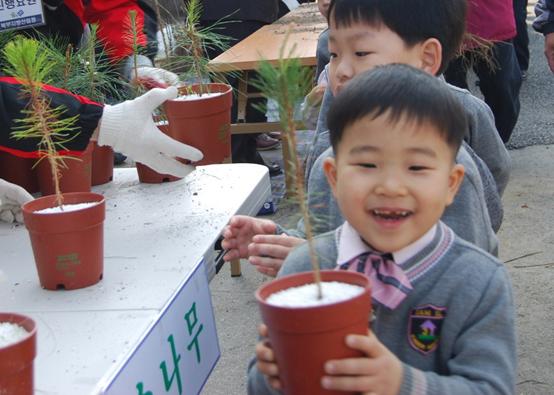 내나무 갖기 캠페인에서 한 아이가 나무를 받아들고 해맑게 웃고 있다. <저작권자(c) 연합뉴스, 무단 전재-재배포 금지>
