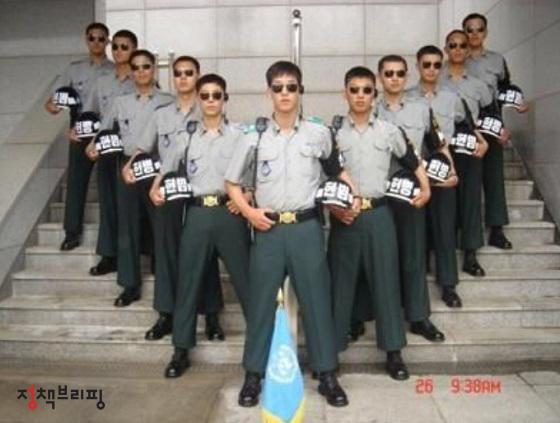 이정우 씨(왼쪽에서 두 번째)가 JSA 코든 병사만이 입을 수 있는 군복을 입고 전우들과 자세를 취하고 있다.