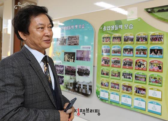진영진 대성동초등학교 교장선생님이 역대 졸업생들 사진을 보며 설명을 하고 있다.