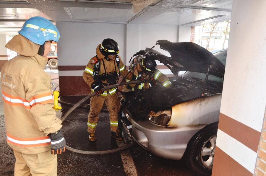 빌라주차장에서 차량에 화재가 발생하여 불을 끄는 작업을 하고 있다