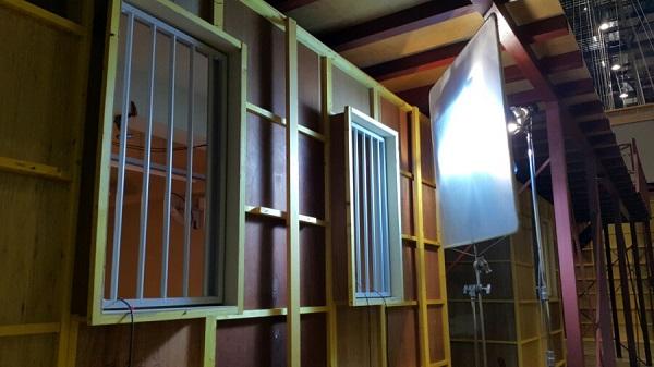 교도소의 철장을 재현한 창문을 비추고 있는 조명 장비.