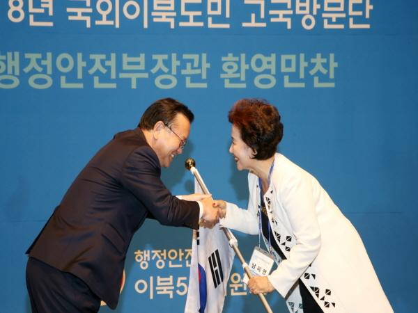 국외이북도민 고국방문단 대표 남혜영씨에게 태극기를 전달하고 있다. <사진=이북5도위원회>