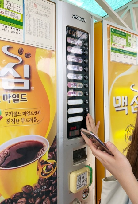성인 여성이 똑바로 일어서서 손을 뻗어야만 음료 메뉴 버튼을 누를수 있다.